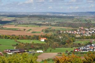 Panoramablick über eine flache, von Wiesen und Äckern durchzogene Landschaft. Rechts im Bild befindet sich eine Siedlung, links ein heller Steinbruch. Im Hintergrund rechts steigen bewaldete Höhenzüge auf.