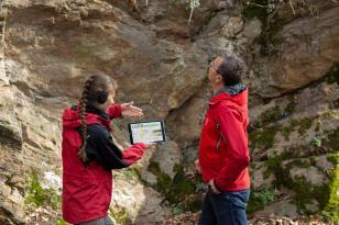 Das Foto zeigt zwei Geowissenschaftler vor einer Felswand. Sie betrachten auf einem Tablet die Informationen der Internetplattform LGRBwissen