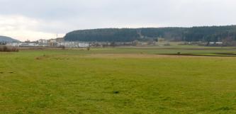Das Bild zeigt flaches Grünland mit einigen Ackerstreifen im Mittelgrund. Von rechts laufen bewaldete Hänge bis fast zum linken Rand. Im Durchlass sind die Häuser einer größeren Stadt erkennbar.