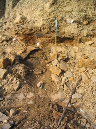 Blick in eine Baugrube. Zu sehen ist hellbraunes bis rötliches Gestein, teilweise als Schutt liegend. Eine Messlatte im oberen, festen Teil sowie Werkzeuge dienen als Größenvergleich.