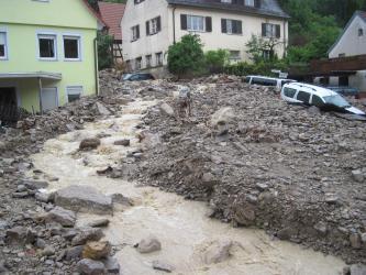 Im Vordergrund fließt ein brauner Bach über unsortiertes Lockermaterial bis Blockgröße. Dahinter befinden sich mehrere Wohnhäuser, die teils mehrere Meter tief vom Lockermaterial eingeschlossen sind. Einige Autos sind ebenfalls in den Massen eingegraben.