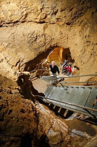 Blick von oben in eine Höhle. In das braune Gestein sind Durchgänge gebrochen, in die Stein- und Metalltreppen eingebaut wurden.