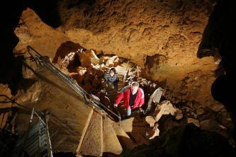 Blick von oben in den Schacht einer Höhle. Stein- und Metalltreppen führen Besucher von unteren Sohlen nach oben.