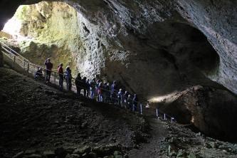 Das Foto zeigt Besucher beim Abstieg in eine hallenartige Höhle. Ein schmaler, gesicherter Laufgang führt dabei schräg vom hellen Eingangsbereich oben links nach rechts unten ins Dunkel der Höhle. Im Vordergrund befindet sich ein Fels- und Geröllhang.