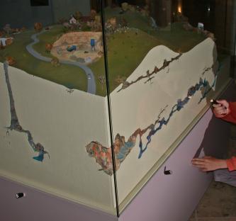 Das Bild zeigt ein dreidimensionales Modell einer Höhle, ausgestellt in einem Glaskasten. Links führt ein steiler Gang abwärts, rechts ist ein waagrechtes, weit verzweigtes Höhlenlabyrinth zu sehen. Darüber befindet sich eine Landschaft mit Steinbruch.