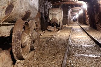 Blick aus der Hocke auf Gleise und Beförderungswagen eines Bergwerkes. Rechts führen die Gleise geradeaus in einen beleuchteten Schacht.