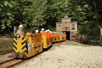 Blick auf die Grubenbahn eines ehemaligen Bergwerkes. Die gelben Wagen sind mit Besuchern besetzt, die orange Jacken und weiße Helme tragen. Im Hintergrund der mit Zinnen bekrönte Eingang des Bergwerkes.
