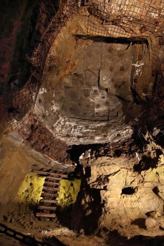 Blick in das Innere eines Besucherbergwerkes. Gezeigt wird ein hoher Raum mit hellem Gestein unten und rötlich braunem Gestein oben. Oben sind teilweise Eisengitter angebracht. Unten links ist eine kleine Leiter aus Eisenschienen zu erkennen.