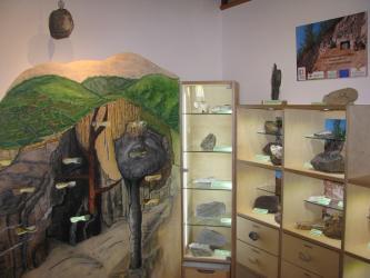 Blick in einen Museumsraum. Rechts sind Regale und ein Schaukasten mit Gesteinsstücken aufgebaut. Links ist eine Schnittzeichnung vom geologischen Aufbau des Kaiserstuhls zu sehen.