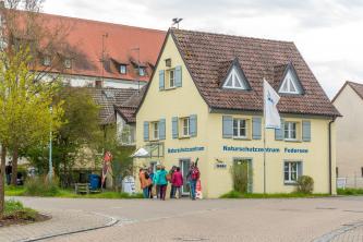 Blick auf ein älteres, kleines gelbes Haus mit blaugrauen Fensterläden. Es hat einen überdachten Eingang und trägt eine Inschrift: Naturschutzzentrum Federsee. Vor dem Eingang steht eine Besuchergruppe.