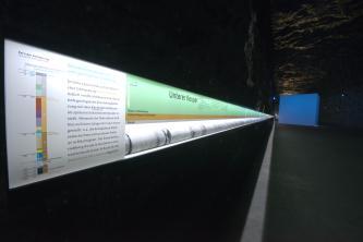 Perspektivischer Blick auf einen mehrere Meter langen Bohrkern, ausgestellt in einer verglasten und beleuchteten Vitrine. Der Bohrkern ist Teil eines Besucherbergwerks und befindet sich in einem sonst dunklen, höhlenartigen Raum.