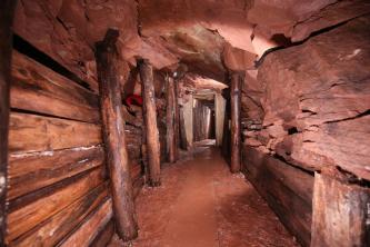 Blick in einen Bergwerksstollen. Die Seitenwände sind teilweise mit Holzbohlen verkleidet, die gewölbte Decke ist mit Stammholz gestützt. Das freiliegende, zerklüftete Gestein ist rötlich braun.