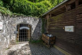 Neben einem mit Holz verkleideten Gebäude rechts grenzt links eine winkelige graue Steinmauer an. In der Mauer befindet sich der vergitterte Eingang zu einem Besucherbergwerk. Ein kleiner hölzerner Transportwagen lehnt an Mauer und Gebäude.