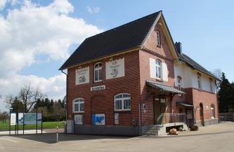 Blick auf das historische Bahnhofsgebäude in Gerstetten. Das mehrteilige Bauwerk beherbergt ein Riffmuseum sowie ein Eisenbahnmuseum. Rechts, im quergestellten Hauptgebäude, ist der überdachte Eingangsbereich mit kleiner Treppe zu sehen.