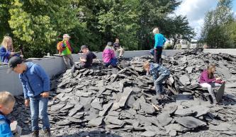 Blick auf mehrere große Haufen von Schieferbruchstücken, aus denen Kinder Fossilien herausklopfen.