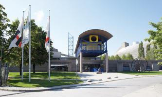 Blick auf den Eingangsbereich von Museum und Werkforum der Holcim GmbH. Der Eingang ist überdacht und von Säulen gestützt. Unter dem gewölbten Dach des Überbaus ist ein stilisiertes Auge angebracht. Links stehen mehrere Fahnenmasten.