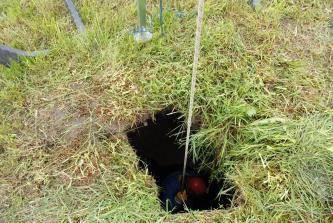 Zu sehen ist ein Loch im von Gras bedeckten Erdboden. An einem Seil wird eine Person in das Loch abgelassen.