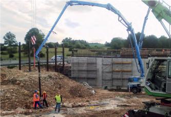 Das Bild zeigt eine Baustelle. Am rechten Bildrand sind zwei Baustellenfahrzeuge zu sehen. In der Bildmitte stehen mehrere Bauarbeiter in einer Gruppe zusammen und halten ein Rohr in eine Öffnung, welches an einem langen Kranarm hängt.