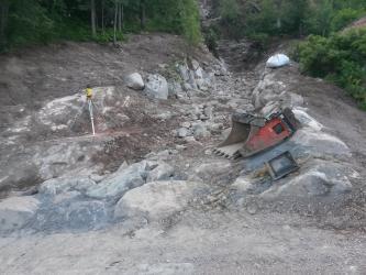 Das Bild zeigt ein Bachbett, in dem gerade kein Wasser fließt. Große Steinblöcke säumen das Ufer, im Bachbett befindet sich Geröll und kleinere Steinblöcke. Am unteren Bildrand verläuft ein neu befestigter Weg. Am Rand liegt eine Baggerschaufel.