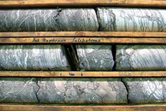 Das Bild zeigt drei rundlich geformte, grauweiß marmorierte Gesteinskörper, die auf Brettern gelagert sind.