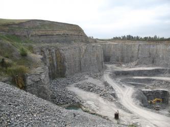 Das Bild zeigt einen großen, zur rechten Bildhälfte geöffneten Steinbruch. Die steilen Wände bestehen aus grauem, im oberen Bereich horizontal geschichteten Gestein.