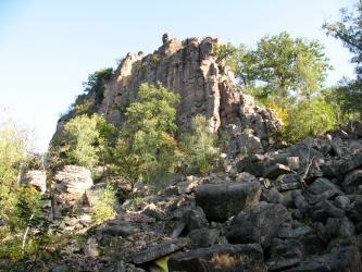Blick auf steil aufragende, von Bäumen und Büschen umstandene rötliche Felszinnen. Im Vordergrund rechts liegen angehäufte Gesteinsbrocken.