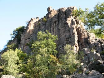 Das Bild zeigt von Bäumen und Gebüsch umstandene, steil aufragende rötliche Felstürme.