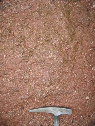 Nahaufnahme von rötlich grauem Gestein mit winzigen dunkelgrauen Einschlüssen. Ein Hammerkopf zeigt die Größenverhältnisse an.