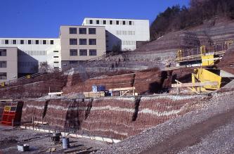 Mehrstufige, nach rechts hin ansteigende Baugrube vor modernen Gebäuden aus in Schichten gelagertem, dunkelrotem und weißem Gestein.