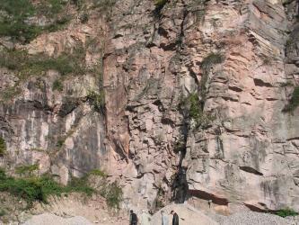 Das Bild zeigt hoch aufragende, graue bis rötliche Felswände, die sich aus unterschiedlich großen Blöcken zusammensetzen. Im linken Bildteil ist Pflanzenbewuchs erkennbar.