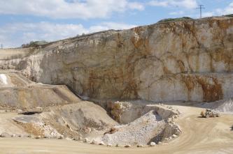 Blick in einen Steinbruch. Beherrschend ist eine nach rechts ansteigende, rot- und hellbraun gefärbte Wand mit Wolkenmuster. Im Vordergrund sind Fahrstraßen, eine Grube sowie nach links ansteigende Gesteinsstufen zu sehen. Rechts unten steht ein Radlader.