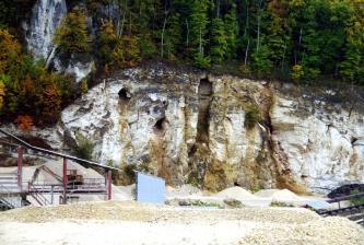 Blick auf eine weißlich bis bräunlich graue Steinbruchwand mit senkrechten Furchen und Felslöchern. Das links abgerundete Gestein ist auf der Kuppe sowie links bewaldet.