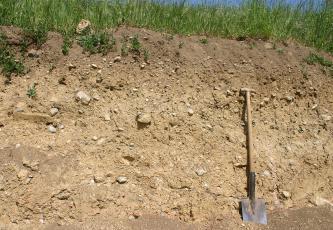 Blick auf eine Böschung, deren Kuppe bewachsen ist. Der mit Steinen durchsetzte Boden ist oben braun, sonst gelblich braun. Rechts ist ein Spaten angelehnt.