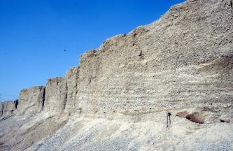 Seitenansicht einer sich nach links verjüngenden, abgestuften Steinbruchwand. Am Fuß des weißlich grauen Gesteins sind Kieshänge.