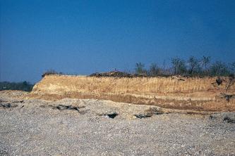 Das Bild zeigt eine graue Schotterfläche, über der sich wie eine Insel rötlich braunes Gestein erhebt. Die Kuppe der Insel ist rechts dünn bewachsen.