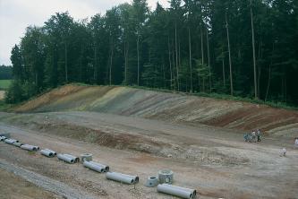 Blick auf eine Straßenbaustelle mit Röhren und Verbindungsstücken im Vordergrund, einer nach links an- und wieder absteigenden Rampe und einem angeschnittenen, bewaldeten Hang im Hintergrund. Der Hang weist schräg verlaufende, unterschiedliche Farben auf.