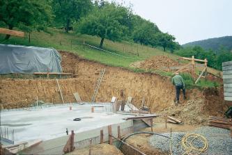 Eine Baugrube wurde in einen von Bäumen bewachsenen, nach links hin ansteigenden Hang eingeschnitten. Die Ränder der Grube zeigen rund um das bereits gegossene Fundament eines Hauses eine gelbbraune Farbe.