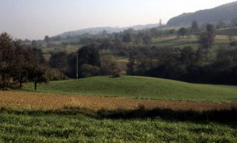 Im Bildmittelpunkt steht ein flacher grüner Hügel. Zum Vordergrund hin schließen sich Äcker und Wiesen an. Hinter dem Hügel ist ein nach rechts ansteigender, von Bäumen gesäumter Gegenhang zu sehen.
