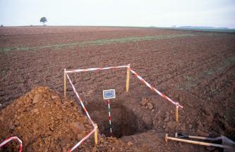 Das Bild zeigt ein aufgegrabenes Bodenprofil inmitten einer weiten, rötlich braunen Ackerfläche.