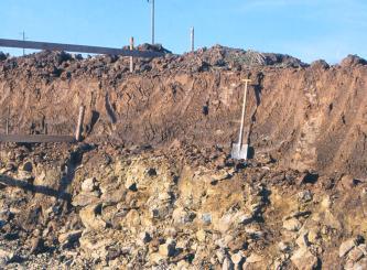 Das Bild zeigt die Profilwand eines zweigeteilten, stufigen Bodens. Während die obere Stufe rötlich braun und steinfrei ist, sind in der unteren, gelblich braunen Stufe größere Steine beigemischt.