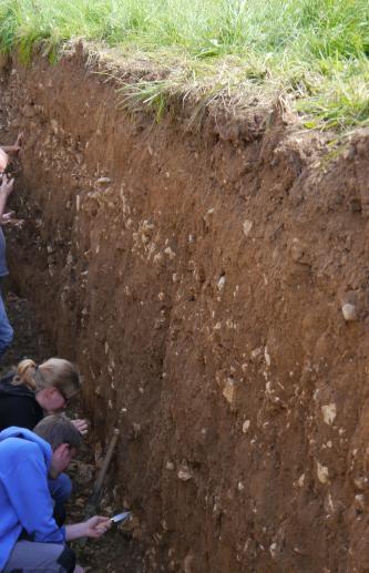 Schrägaufnahme eines sehr tiefen, aufgegrabenen Bodenprofils unter Grünland. Im dunkelbraunen Boden sind mehrere Steinlagen erkennbar. Interessierte Bodenkundler untersuchen das Profil.