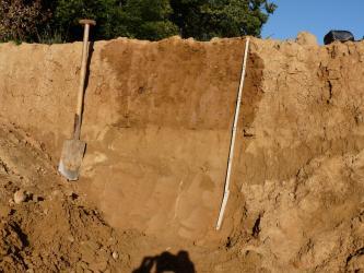 Das Foto zeigt die Seitenwand einer Baugrube mit rötlich braunem Bodenmaterial.  Die Grube ist über 1,20 m tief.