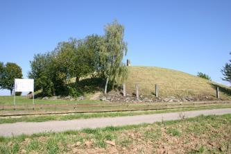 Das Bild zeigt einen nachgebildeten runden Grabhügel mit etwas Baumbestand auf der linken Seite. Unterhalb des sonst kahlen Hügels verläuft ein Zaun sowie ein schmaler Fußweg.