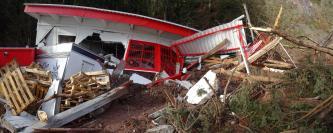 Das Bild zeigt ein zerstörtes Gebäude, dessen Wände unter anderem eingebrochen und das Dach eingedrückt sind. Holz-, Blechteile, Paletten liegen rundherum und ein Imbisswagen liegt umgekippt davor. Schlammmassen mit Baumteilen säumen den rechten Bildrand.
