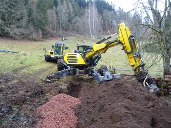 Ein gelber Bagger hebt in der Bildmitte einen Graben aus. Im Hintergrund ist eine Wiese und ein bewaldeter Hang zu erkennen.