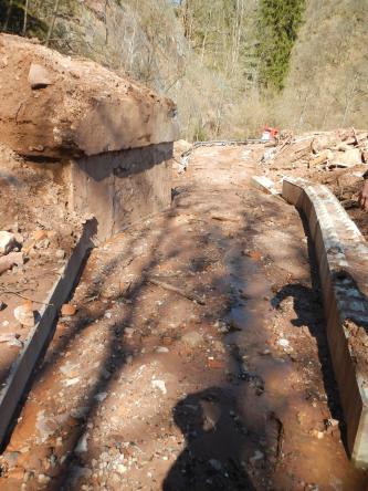 Zu sehen ist ein Entwässerungskanal, in dem und um den herum Schlamm und einige Gesteinsbrocken liegen. Ein Wasserrinnsal fließt in der Mitte. Im Hintergrund sieht man rechts einen Haufen an Trümmerteilen und Schlamm.