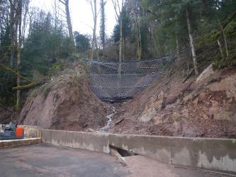 Das Bild zeigt einen tief eingeschnittenen, bewaldeten Hang, in dessen Mitte ein Wasserrinnsal auf eine niedrige Betonmauer zufließt. Über dem Rinnsal ist von einer Hangseite zur anderen ein großes Stahlnetz gespannt.