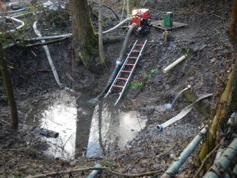 Zu sehen ist eine wassergefüllte Mulde. Aus einem Rohr im Boden läuft weiteres Wasser in die Mulde. Am Rand steht eine Pumpe, die Wasser aus der Mulde pumpt. Drumherum liegen einige Feuerwehrschläuche und eine Leiter.