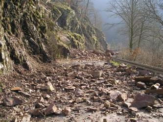 Blick auf eine Straße, die an einem links aufragenden Felshang entlangführt. Die Straße ist mit Steinen und Felstrümmern übersät und somit gerade unbefahrbar.