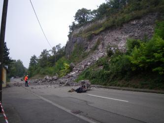 Rechts einer Straße erhebt sich ein felsiger, teils auch bewachsener Hang. Von diesem Hang sind Steine und Felstrümmer auf die Straße gestürzt. Ein Mann in Schutzkleidung links betrachtet den Schaden.